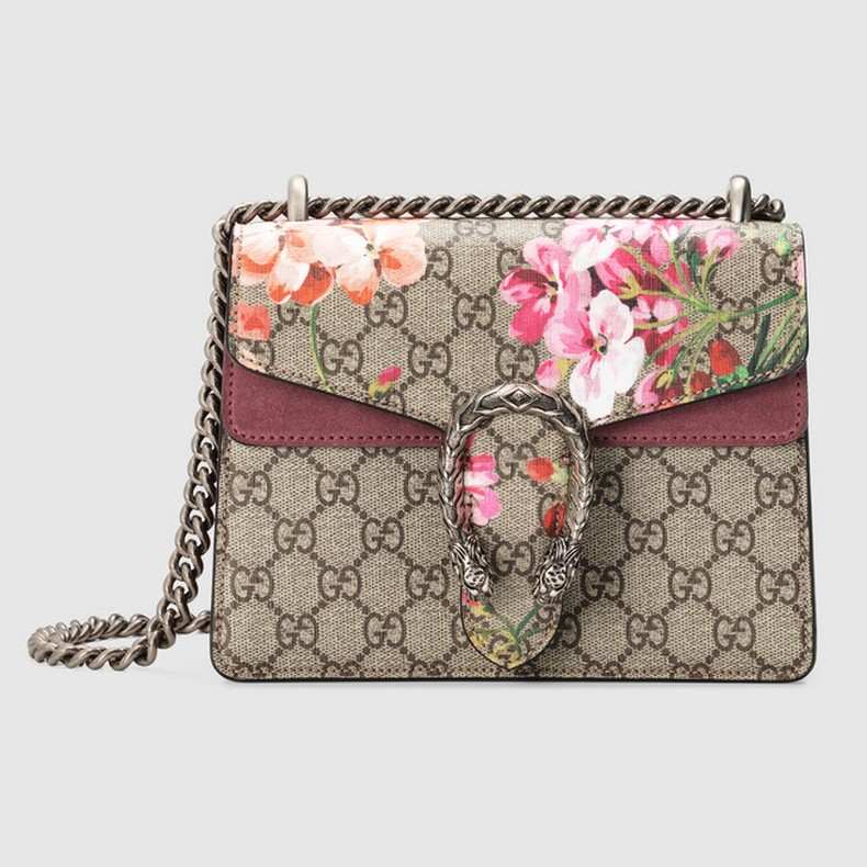 A mini structured bag with our textured tiger head spur closure in Blooms print supreme canvas. The sliding chain strap can be worn multiple ways, changing between a shoulder and a top handle bag.