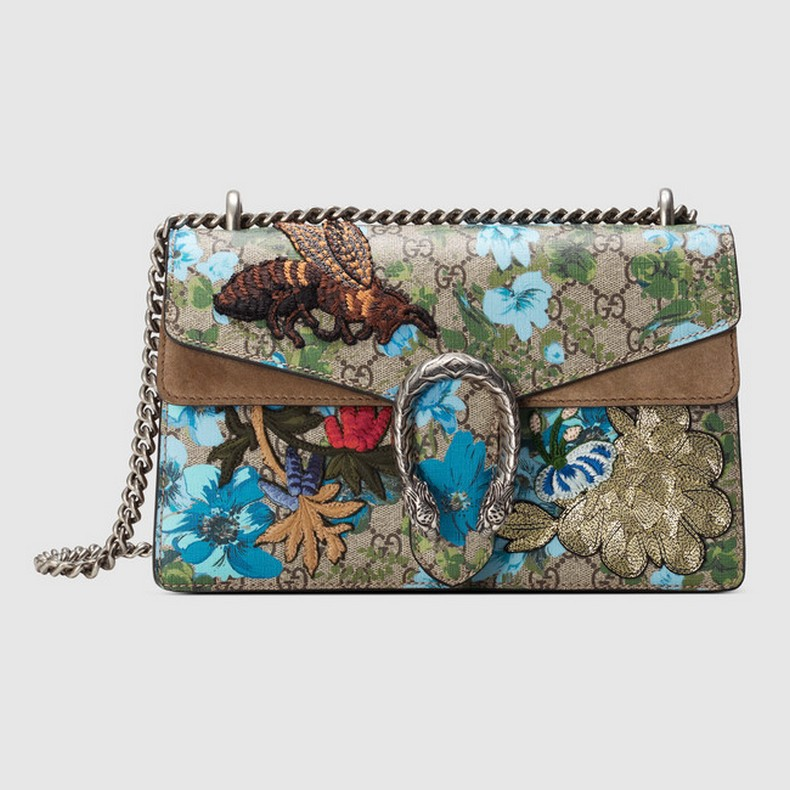 A structured GG Supreme canvas bag with painted flowers and patches with our textured tiger head closure. The sliding chain strap can be worn multiple ways, changing between a shoulder and a top handle bag.