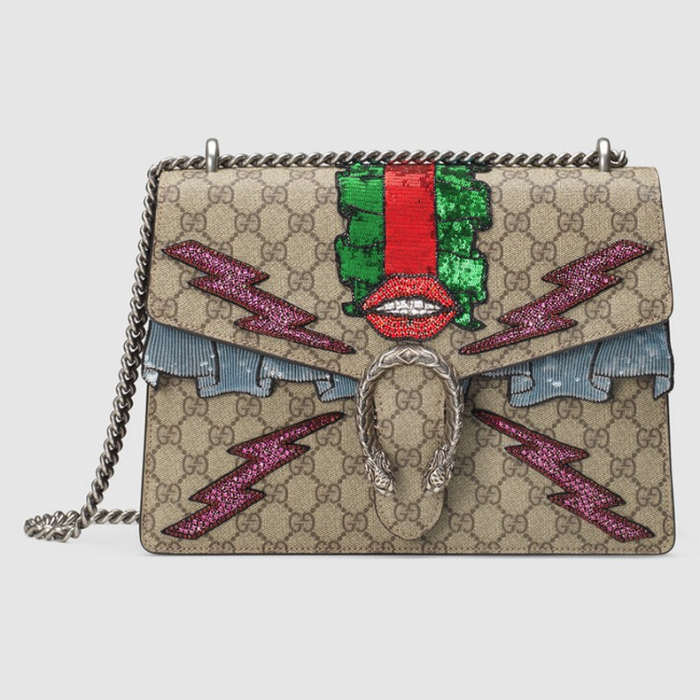 This shoulder bag has a textured tiger head spur closure with hand-embroidered appliqués depicting a mouth and lightening bolts. The sliding chain strap can be worn multiple ways, changing between a shoulder and a top handle bag.