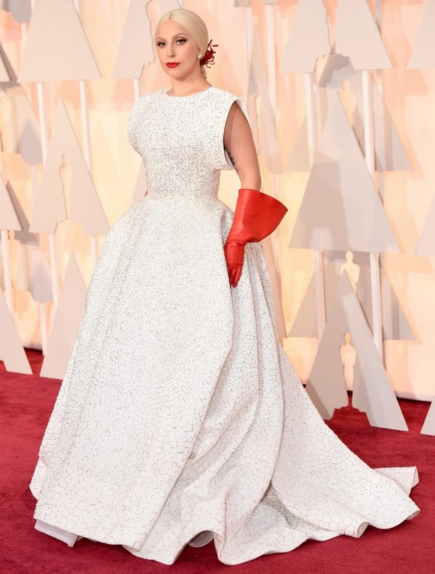 Lady Gaga was wearing a custom glittery white gown by Tunisian-born designer Azzedine Alaia paired with plastic red gloves